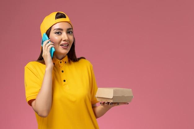 Vooraanzicht vrouwelijke koerier in geel uniform en cape die voedselpakket vasthoudt en aan de telefoon spreekt op de lichtroze muur. Gratis Foto