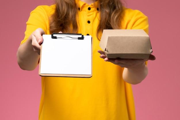 Vooraanzicht vrouwelijke koerier in geel uniform en cape met kleine notitieblok voor bezorgvoedselpakket op roze muur, servicebaan werkbezorging uniform Gratis Foto