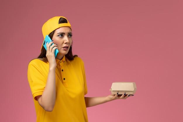 Vooraanzicht vrouwelijke koerier in geel uniform en cape met voedselpakket en praten aan de telefoon op de lichtroze muur bedrijf uniforme bezorgdienst Gratis Foto