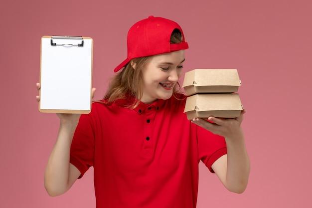 Vooraanzicht vrouwelijke koerier in rood uniform en cape met blocnote en kleine bezorgvoedselpakketten lachen om lichtroze achtergrondservice uniforme bezorging Gratis Foto