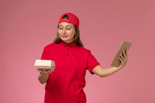 Vooraanzicht vrouwelijke koerier in rood uniform en cape met klein voedselpakket en blocnote op roze muur, uniform bezorger servicebedrijf Gratis Foto