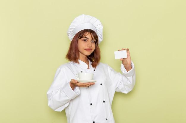 Vooraanzicht vrouwelijke kok in wit kok pak met kopje thee en kaart op het groene oppervlak Gratis Foto