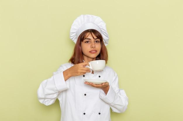Vooraanzicht vrouwelijke kok in wit kokkostuum het drinken van thee op groen oppervlak Gratis Foto