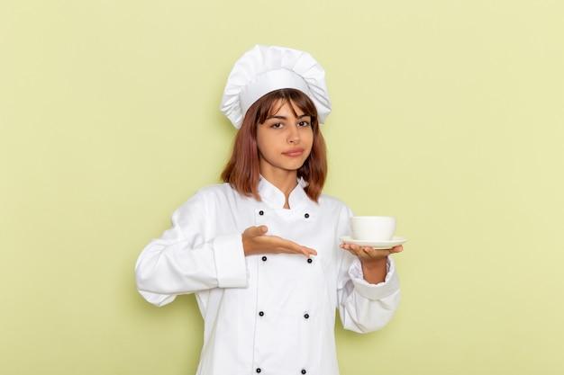 Vooraanzicht vrouwelijke kok in witte kok pak houden kopje thee op groene ondergrond Gratis Foto