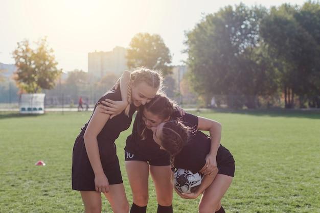 Vooraanzicht vrouwelijke voetballers omarmen Gratis Foto