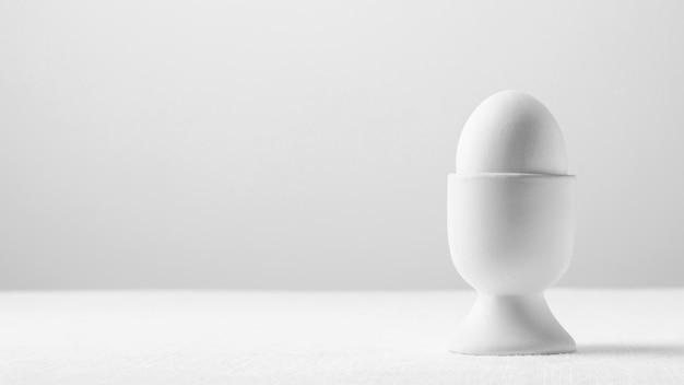 Vooraanzicht wit ei in standaard met kopie-ruimte Gratis Foto