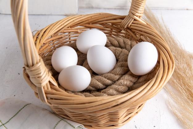 Vooraanzicht witte hele eieren in mand op de witte achtergrond. Gratis Foto