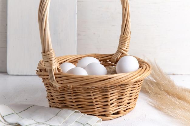 Vooraanzicht witte hele eieren in mand op wit bureau. Gratis Foto