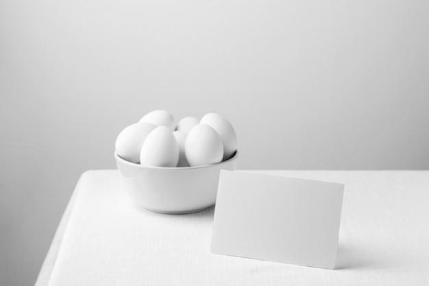 Vooraanzicht witte kippeneieren in kom met lege nota Gratis Foto