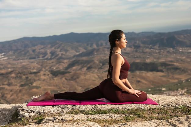 Vooraanzicht yoga pose op mat met jonge vrouw Gratis Foto