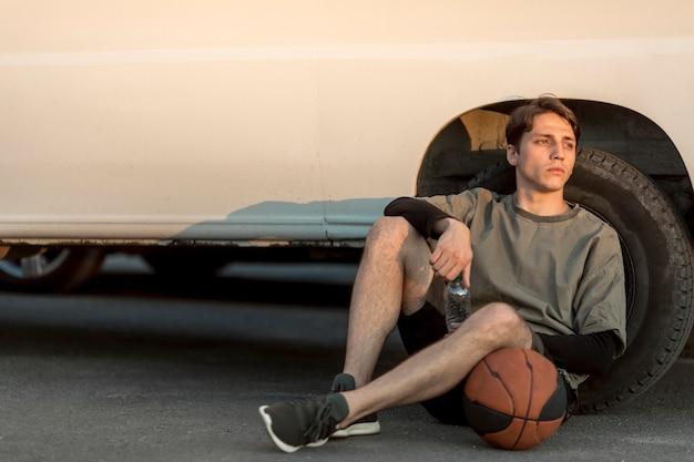 Vooraanzicht zittende man met basketbal Gratis Foto