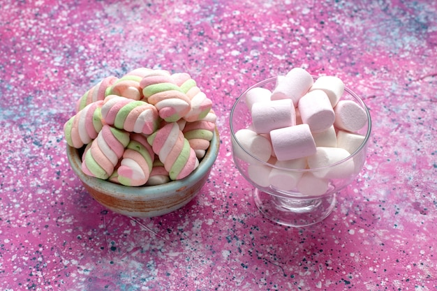 Vooraanzicht zoete gekleurde marshmallows gevormd in ronde pot met witte op roze bureau. Gratis Foto