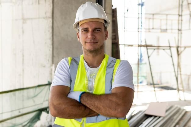 Vooraanzichtarbeider in bouw die beschermende uitrusting draagt Gratis Foto