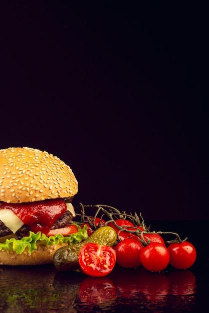 Vooraanzichthamburger met zwarte achtergrond Gratis Foto