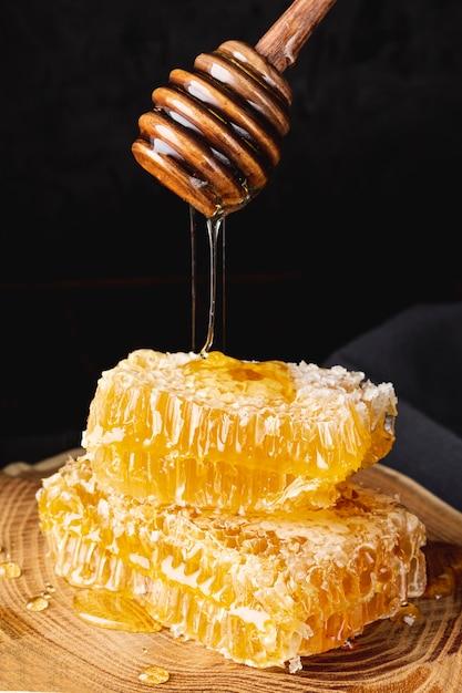 Vooraanzichthoning die van lepel op gouden honingraten druipt Gratis Foto