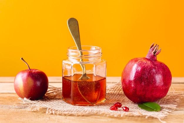 Vooraanzichthoningpot met lepel en fruit Gratis Foto