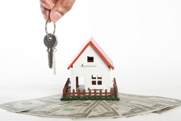 Vooraanzichthuis en geld met de sleutels van de persoonsholding Gratis Foto