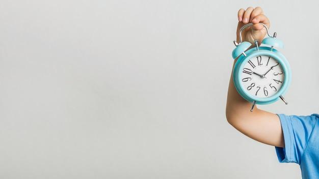 Vooraanzichtjong geitje dat een klok houdt Premium Foto