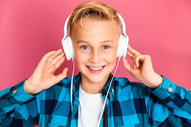 Vooraanzichtjongen het luisteren muziek bij hoofdtelefoons Gratis Foto