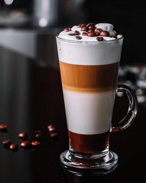 Vooraanzichtkoffie latte met koffiebonen Gratis Foto