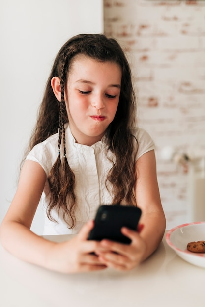Vooraanzichtmeisje met telefoon en mondhoogtepunt van koekjes Gratis Foto