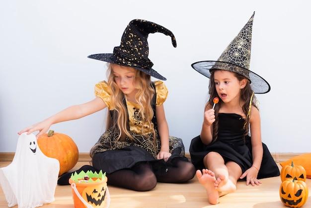 Vooraanzichtmeisjes die op vloer op halloween zitten Gratis Foto