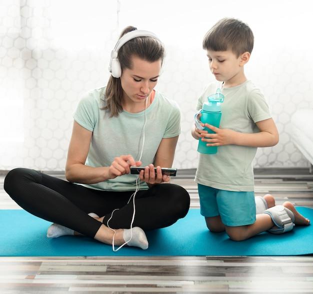 Vooraanzichtmoeder samen met zoon op yogamat Gratis Foto