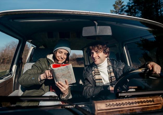 Vooraanzichtpaar dat een kaart bekijkt terwijl over de weg struikelt Gratis Foto