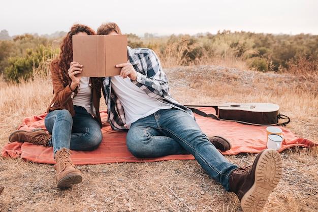 Vooraanzichtpaar dat op een boek kijkt Gratis Foto