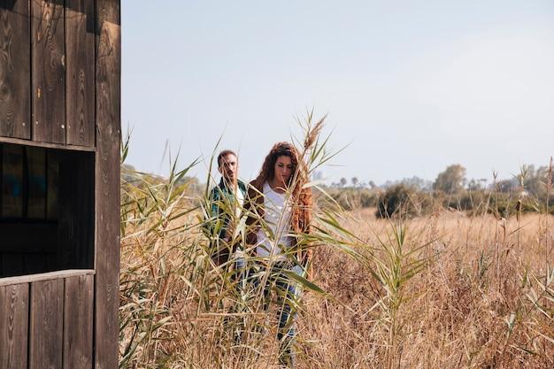 Vooraanzichtpaar dat op een tarwegebied loopt Gratis Foto