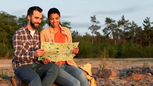 Vooraanzichtpaar dat samen op een kaart kijkt Gratis Foto
