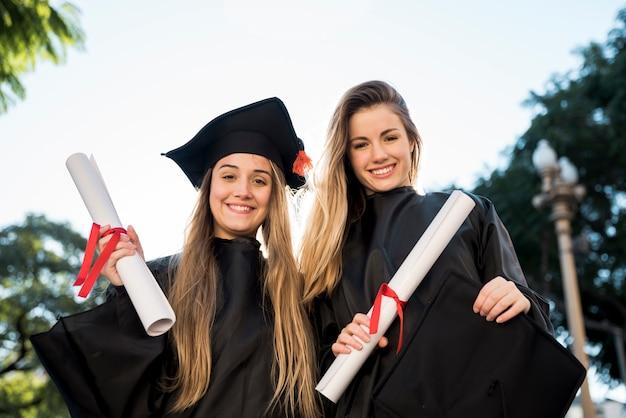 Vooraanzichtvrienden die een diploma behalen die de camera bekijken Gratis Foto