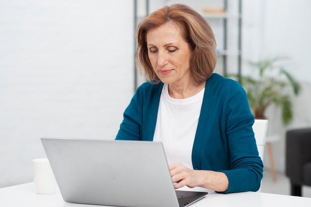 Vooraanzichtvrouw die aan laptop werkt Gratis Foto