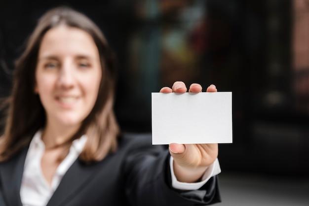 Vooraanzichtvrouw die een adreskaartje houdt Gratis Foto