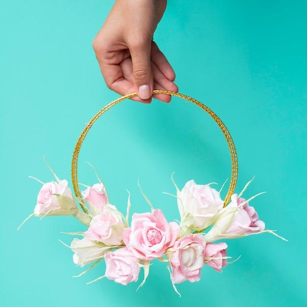 Vooraanzichtvrouw die een bloemenframe op blauwe achtergrond houdt Gratis Foto