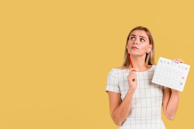 Vooraanzichtvrouw die haar periodekalender met exemplaarruimte toont Premium Foto