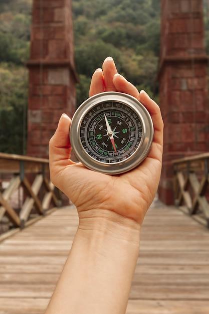 Vooraanzichtvrouw die kompas voor richtingen gebruikt Gratis Foto