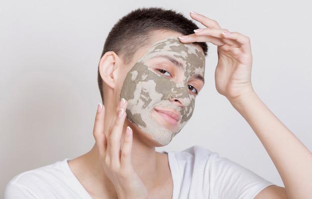 Vooraanzichtvrouw die met gezichtsmasker de camera bekijken Gratis Foto