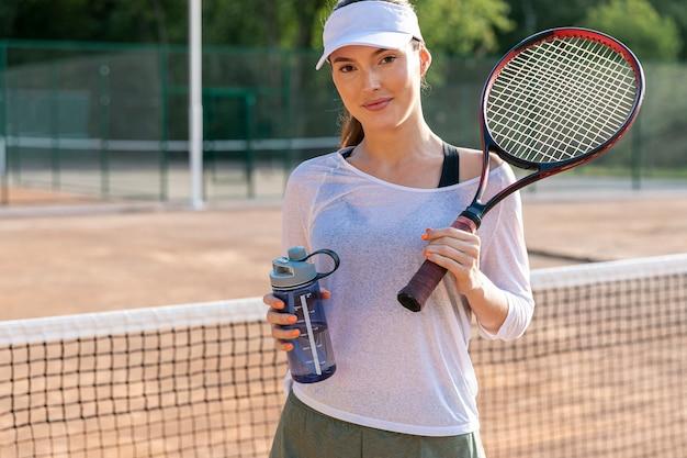 Vooraanzichtvrouw die op tennisbaan hydrateert Gratis Foto