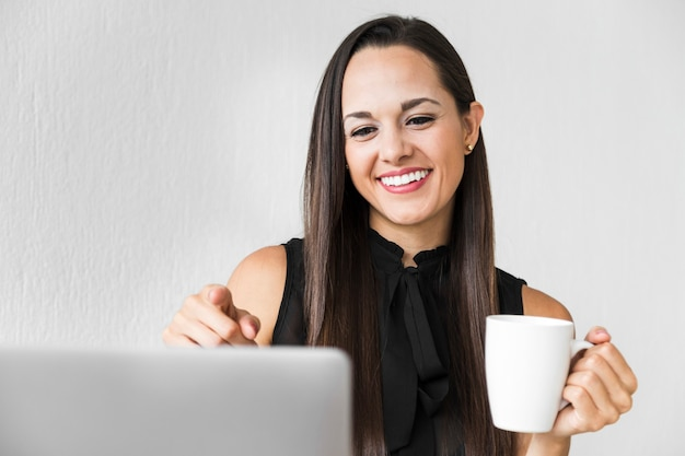 Vooraanzichtvrouw die van haar kop van koffie genieten op het kantoor Gratis Foto