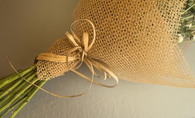 Voorbeeld van het verpakken van een boeket bloemen in een bruin bloemenrooster, close-up Premium Foto
