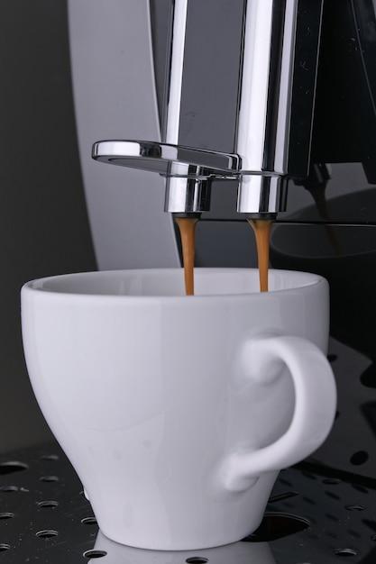 Voorbereiding ochtend zwarte aromatische americano koffiebonen uit professionele koffiemachine. heet wakker Premium Foto