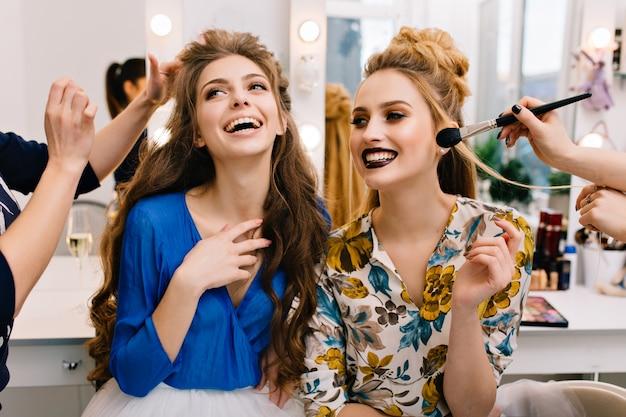 Voorbereiding op groot gezelschap van vrolijke jonge vrouwen in de kapsalon Gratis Foto