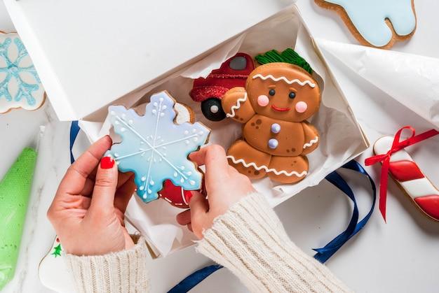 Voorbereiding op kerstmis, versieren van traditionele peperkoek met veelkleurige suiker glazuur, het meisje houdt de koekjes Premium Foto