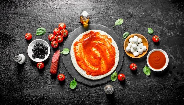 Voorbereiding pizza. deeg met verschillende ingrediënten voor het koken van pizza. op zwarte rustieke achtergrond Premium Foto