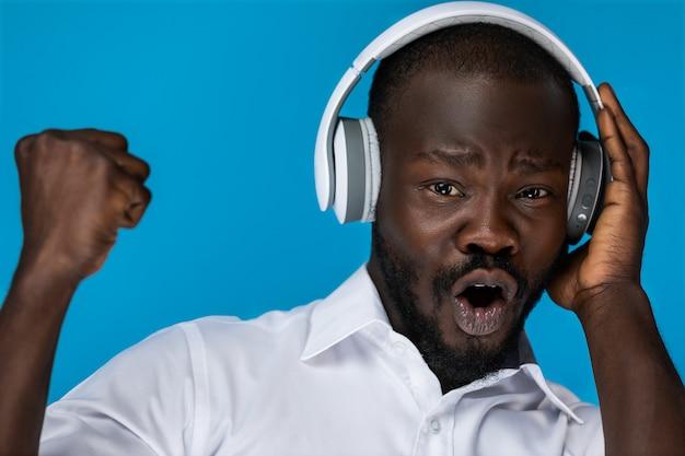 Voorgrond bebaarde afro-amerikaanse man met open ogen stijgende linkerhand Gratis Foto