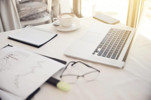 Voorgrond van objecten op de werkplek: brillen, diagrammen, laptop, notebook Gratis Foto
