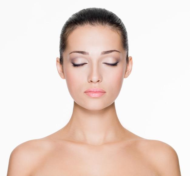 Voorportret van mooi gezicht met mooie gesloten ogen - geïsoleerd op wit Gratis Foto