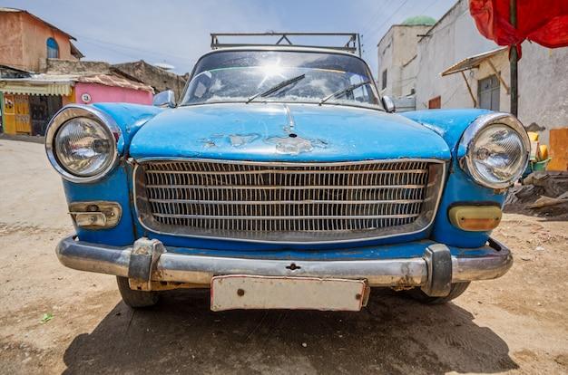 Voorste deel van een oude blauwe 60's auto zeer gebruikt op een onverharde weg. Premium Foto