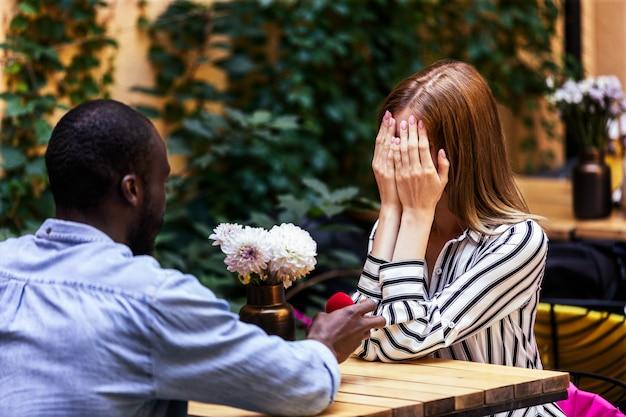 Voorstel van afrikaanse jongen aan een blanke meisje op het terras van een gezellig openluchtrestaurant Gratis Foto